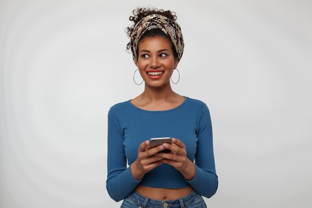 Studio shot van jonge blij vrij krullend brunette vrouw breed glimlachend terwijl opzij kijkt, mobiele telefoon in opgeheven handen houden terwijl poseren op witte achtergrond