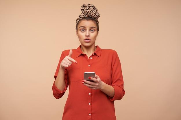 Studio shot van jonge bruinharige vrouw met open ogen die verloren is terwijl ze zich voordeed over beige muur met mobiele telefoon en verbaasd naar de voorkant kijkt