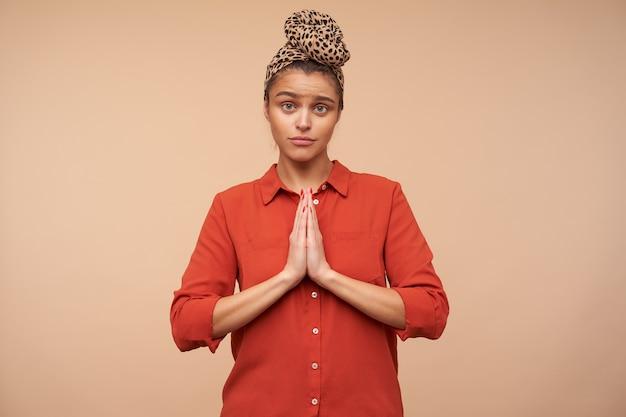 Studio shot van jonge brunette met groene ogen die de handen vasthoudt in een biddend gebaar terwijl ze hopelijk naar de voorkant kijkt en fronst wenkbrauwen, geïsoleerd over beige muur