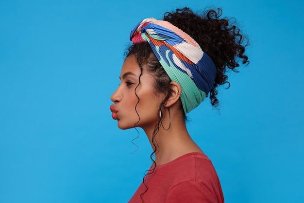 Studio shot van jonge donkerharige krullende vrouw met veelkleurige hoofdband die haar lippen in luchtkus vouwt terwijl ze vooruit kijkt, staande over de blauwe muur