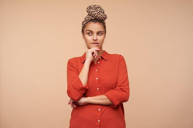 Studio shot van jonge doordachte bruinharige vrouw met hoofdband opgeheven hand op haar kin te houden en peinzend onderlip bijten terwijl poseren over beige muur