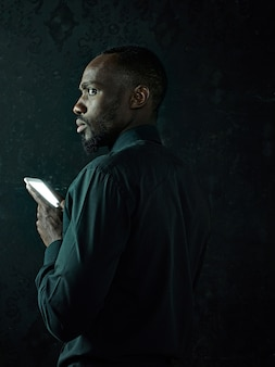 Studio shot van jonge ernstige zwarte afrikaanse man denken tijdens het praten op de mobiele telefoon tegen zwarte studio achtergrond