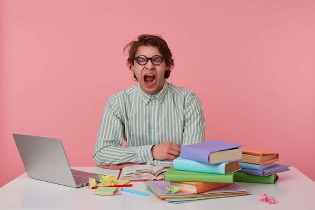 Studio shot van jonge gapende verveelde man met bril, draagt op een leeg shirt, zittend aan een tafel met boeken, werken op een laptop, ziet er moe uit. geïsoleerd op roze achtergrond.