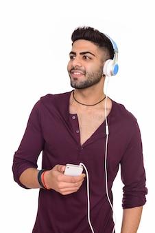 Studio shot van jonge gelukkig indiase man luisteren naar muziek