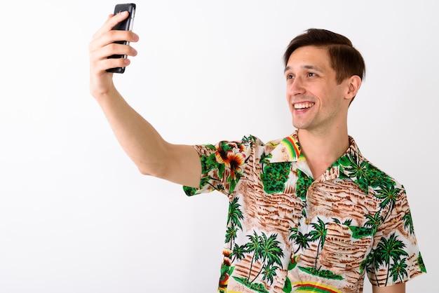 Studio shot van jonge gelukkig toeristische man die lacht terwijl het nemen van zelf