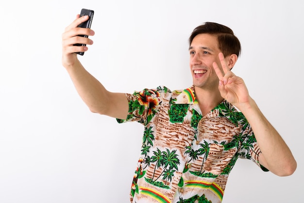 Studio shot van jonge gelukkig toeristische man glimlachend terwijl het geven van peac