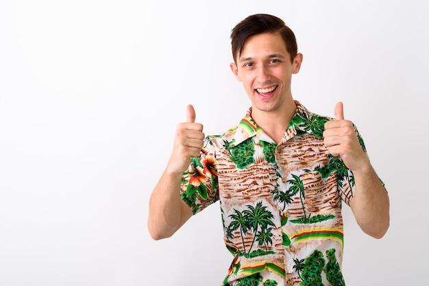 Studio shot van jonge gelukkig toeristische man glimlachend terwijl het geven van thum