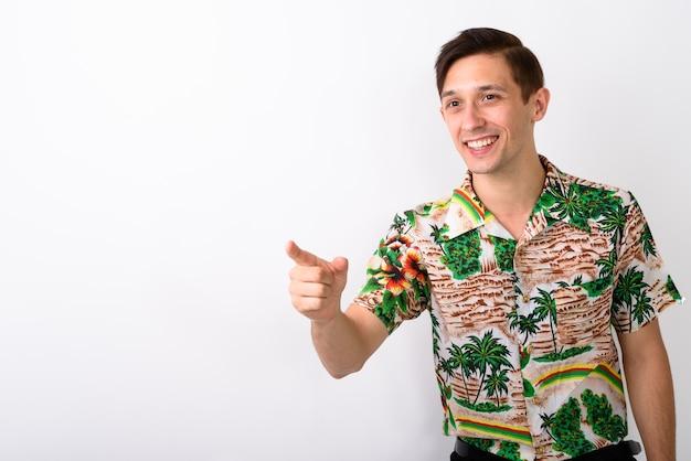 Studio shot van jonge gelukkig toeristische man glimlachend terwijl wijzend op