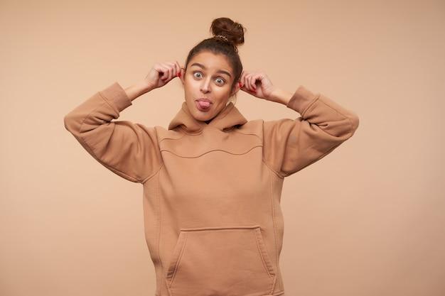 Studio shot van jonge groenogige bruinharige vrouw die grappige gezichten maakt terwijl ze voor de gek houdt en vrolijk tong naar voren toont, geïsoleerd over beige muur