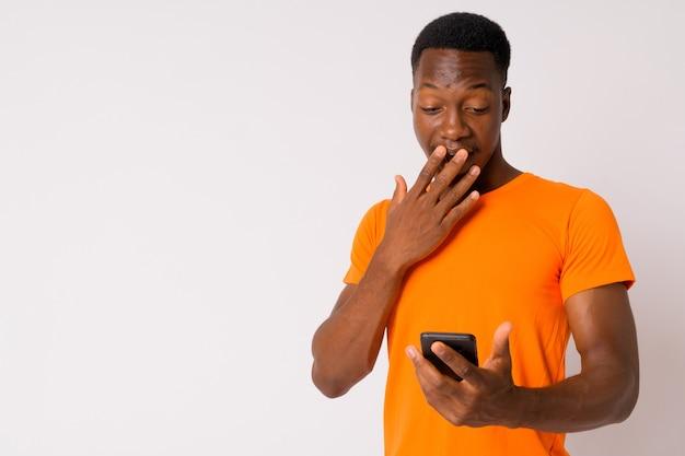 Studio shot van jonge knappe afrikaanse man met afro haar tegen witte achtergrond