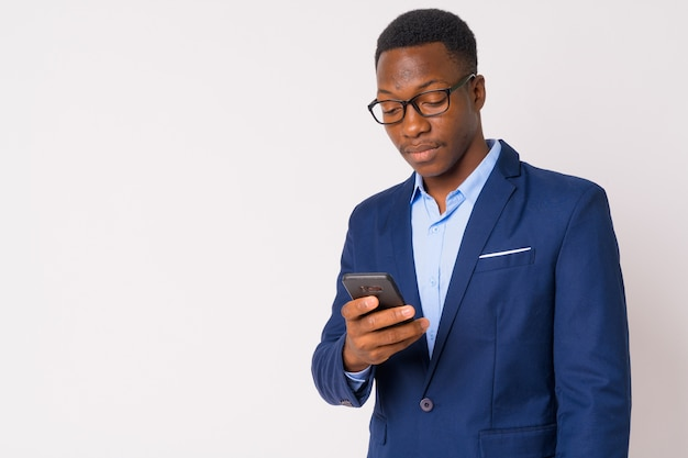 Studio shot van jonge knappe afrikaanse zakenman met afro haar tegen witte achtergrond