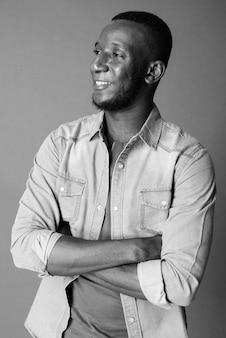 Studio shot van jonge knappe bebaarde afrikaanse man met kort haar tegen grijs in zwart-wit