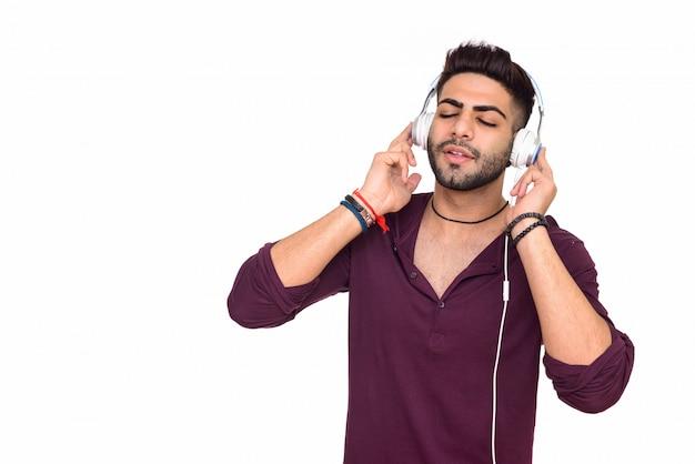 Studio shot van jonge knappe indiase man luisteren naar muziek geïsoleerd op een witte achtergrond