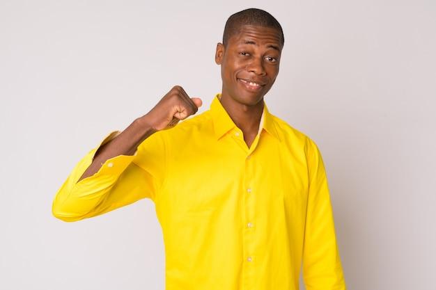 Studio shot van jonge knappe kale afrikaanse zakenman tegen witte achtergrond