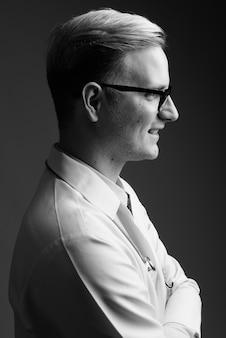 Studio shot van jonge knappe man arts met blond haar tegen grijze muur in zwart en wit