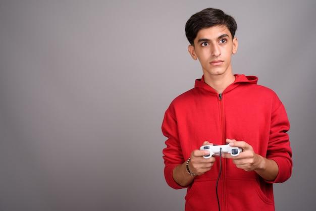 Studio shot van jonge knappe perzische tiener tegen een grijze achtergrond