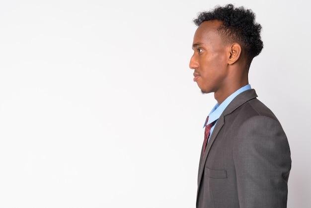 Studio shot van jonge knappe zakenman met afro haar dragen pak tegen wit