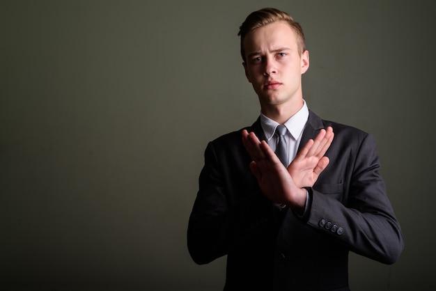 Studio shot van jonge knappe zakenman pak dragen tegen gekleurde achtergrond