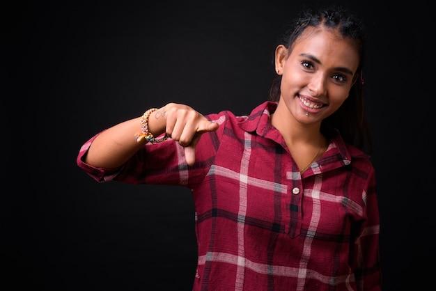 Studio shot van jonge mooie aziatische hipster vrouw met gevlochten haar tegen zwarte achtergrond