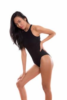 Studio shot van jonge mooie aziatische vrouw in zwembroek naar voren buigen