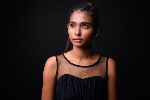 Studio shot van jonge mooie aziatische vrouw met gevlochten haar jurk dragen tegen zwarte achtergrond