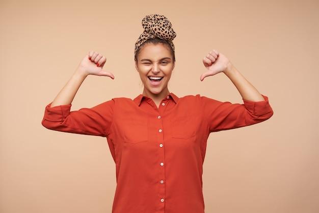Studio shot van jonge mooie bruinharige dame die haar handen omhoog houdt terwijl ze zichzelf laat zien met duimen en vrolijk knipoogt, poseren over beige muur