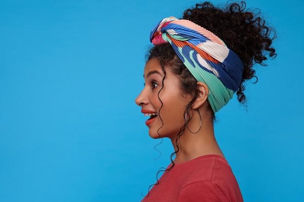Studio shot van jonge mooie bruinharige krullende dame gekleed in bordeauxrood t-shirt verrast haar wenkbrauwen optrekken terwijl ze opgewonden vooruit kijkt, poseren over blauwe muur