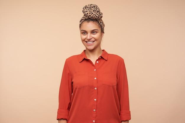 Studio shot van jonge mooie brunette vrouw met hoofdband opzij kijken met charmante glimlach, haar handen langs het lichaam houden terwijl poseren over beige muur
