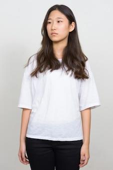 Studio shot van jonge mooie koreaanse vrouw tegen een witte achtergrond