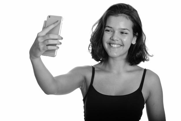 Studio shot van jonge mooie multi-etnische tiener meisje met kort haar geïsoleerd tegen een witte achtergrond in zwart en wit