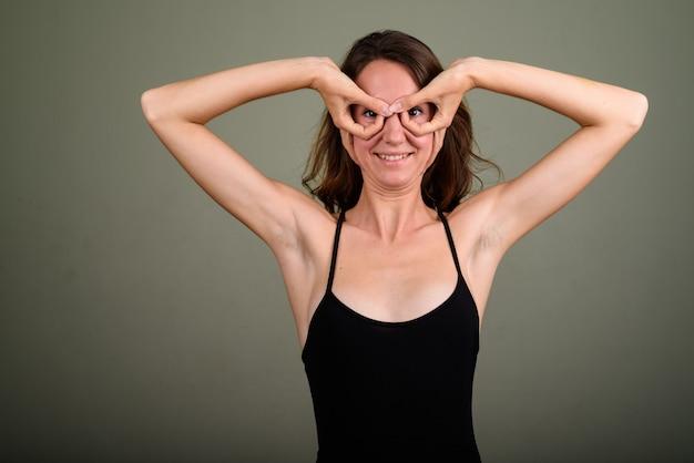 Studio shot van jonge mooie vrouw, gekleed in mouwloze top tegen een gekleurde achtergrond