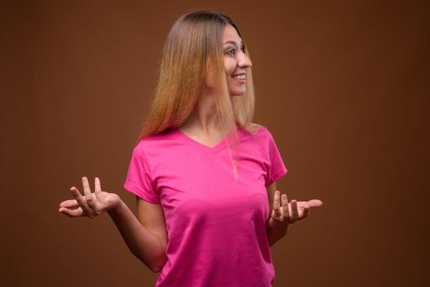 Studio shot van jonge mooie vrouw lachend met armen open tegen bruine muur