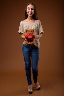Studio shot van jonge mooie vrouw tegen bruine achtergrond