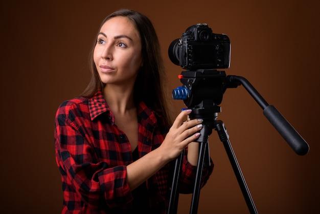 Studio shot van jonge mooie vrouw vloggen tegen bruine achtergrond