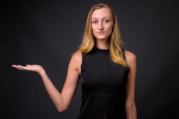 Studio shot van jonge mooie zakenvrouw met sluik blond haar tegen grijs