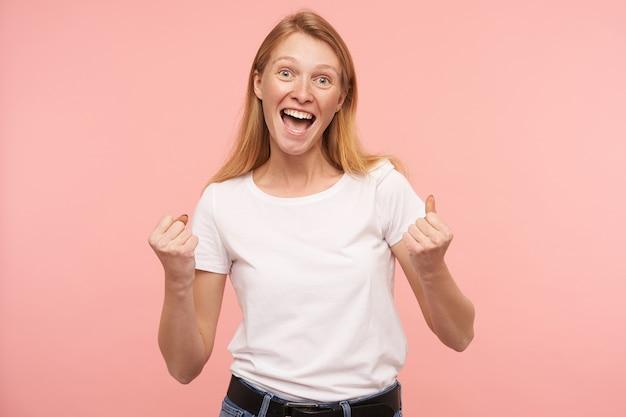 Studio shot van jonge opgewonden mooie roodharige dame die emotioneel handen opheft terwijl ze zich verheugt over iets, het dragen van een basic wit t-shirt terwijl ze over de roze achtergrond staat