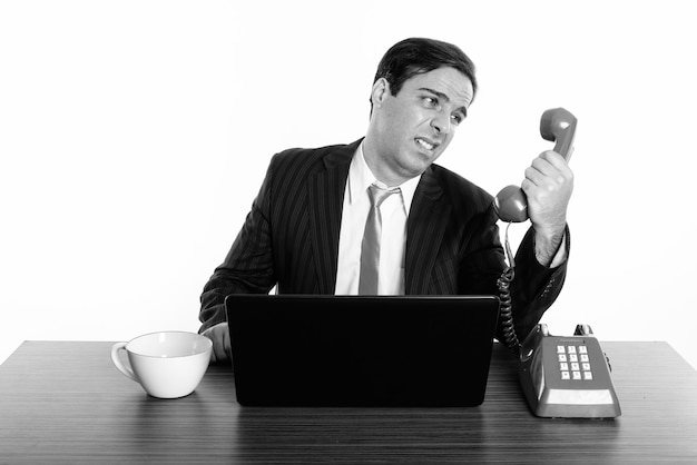 Studio shot van jonge perzische zakenman zittend achter houten bureau geïsoleerd, zwart en wit