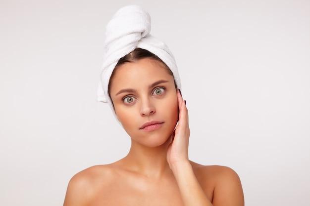 Studio shot van jonge verrast brunette vrouwelijke keping hand op haar gezicht terwijl staande op een witte achtergrond, haar groene ogen afronden terwijl ze naar de camera kijkt