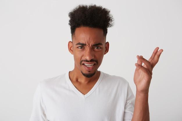 Studio shot van jonge vrij donkere huidskleurige ongeschoren gekrulde man fronst zijn gezicht en houdt de hand omhoog