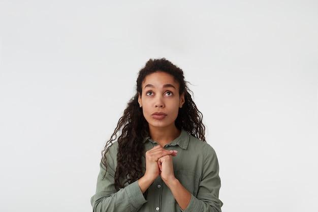 Studio shot van jonge vrij langharige brunette dame met donkere huid opgeheven handen vouwen terwijl hopelijk omhoog kijken, poseren op witte achtergrond