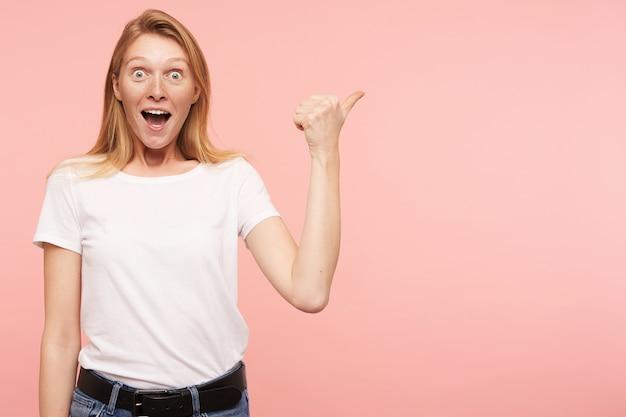 Studio shot van jonge vrolijke roodharige dame met casual kapsel wijzend opzij en verbaasd kijken naar camera met brede mond geopend, geïsoleerd op roze achtergrond
