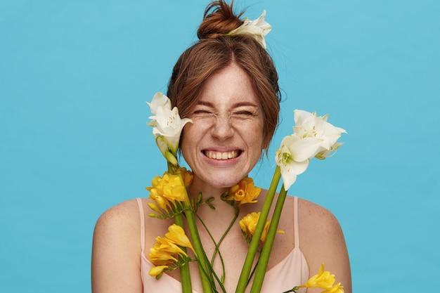 Studio shot van jonge vrolijke roodharige vrouw met broodje kapsel vrolijk haar gezicht fronsen terwijl breed lachend, geïsoleerd op blauwe achtergrond met bos bloemen
