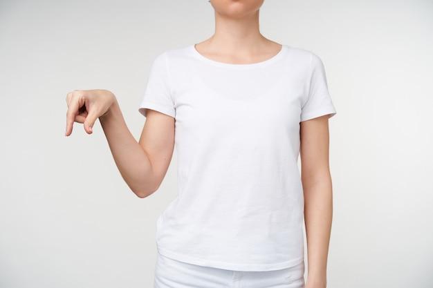 Studio shot van jonge vrouw gekleed in wit t-shirt met letter q met haar vingers tijdens het leren van doof alfabet, geïsoleerd op witte achtergrond
