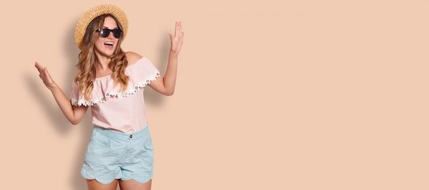 Studio shot van jonge vrouw in modieuze kleding, geniet van de zomertijd, poses op beige met kopie ruimte voor uw advertentie of promotionele inhoud. lifestyle concept