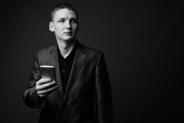 Studio shot van jonge zakenman die mobiele telefoon gebruikt tegen grijze muur