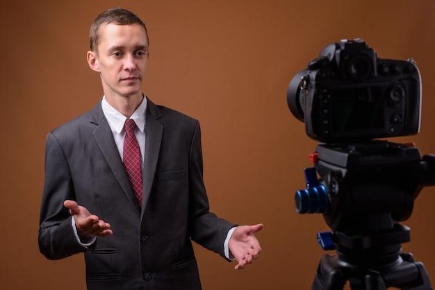 Studio shot van jonge zakenman op bruin