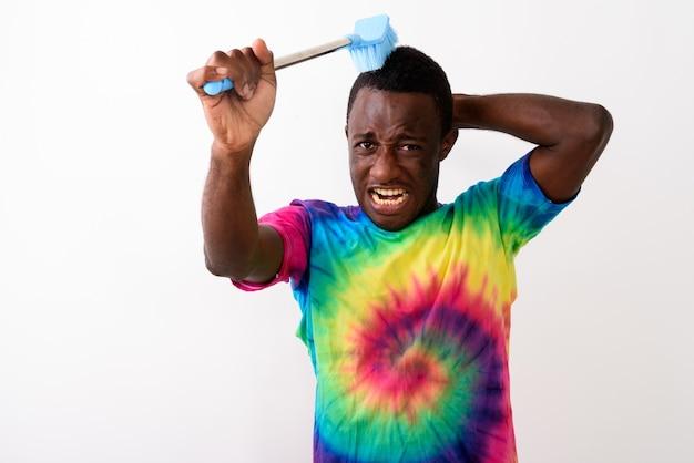 Studio shot van jonge zwarte afrikaanse man met behulp van schoonmaakborstel w