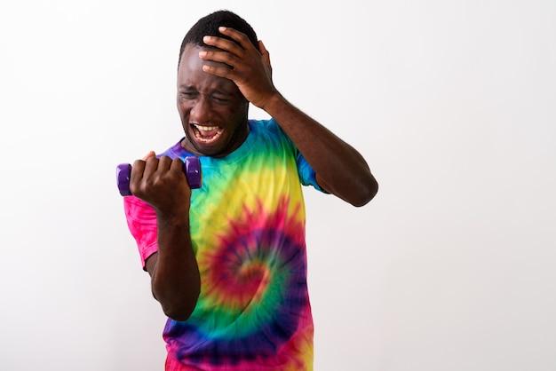 Studio shot van jonge zwarte afrikaanse man moe terwijl flexi