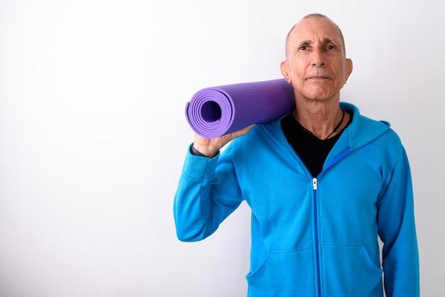 Studio shot van kale senior man met yoga mat klaar voor sportschool tegen witte achtergrond