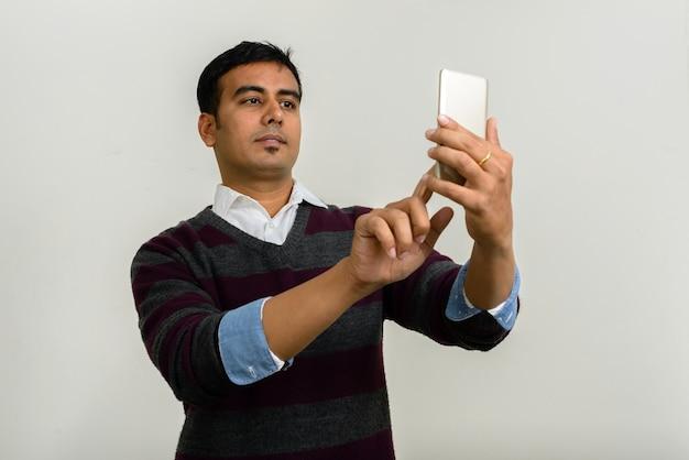 Studio shot van knappe indiase man tegen witte achtergrond